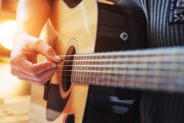 Guitarrista toca la guitarra sobre fondo de madera