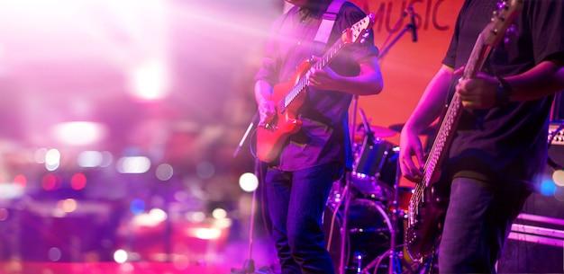 Guitarristas con iluminación colorida en un escenario