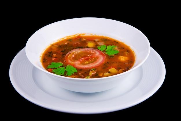 Gulash húngaro: sopa espesa de verduras con carne y tomates en boul blanco.