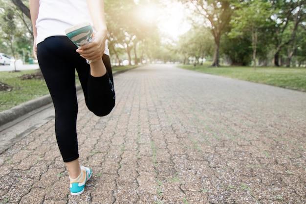 Gusano del corredor deportivo y ejercicio antes de correr, entrenamiento de la mujer en el parque