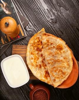 Gutab caucásico tradicional, kutab, gozleme con sumakh y yogurt en placa de madera.