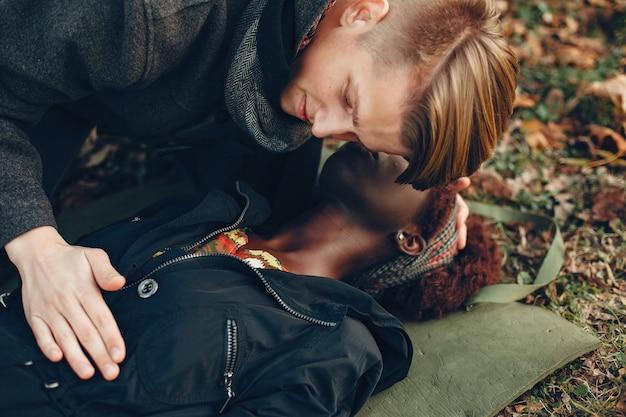 Guy ayuda a una mujer. la chica afro está inconsciente. proporcionar primeros auxilios en el parque.