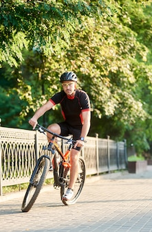 Guy biker montando en bicicleta cerca del parque verde