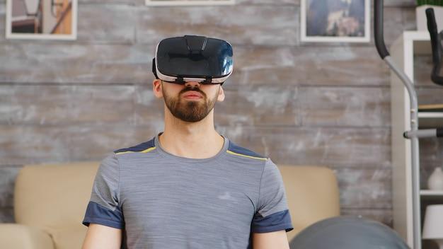 Guy se centra en respirar haciendo yoga con casco de realidad virtual.