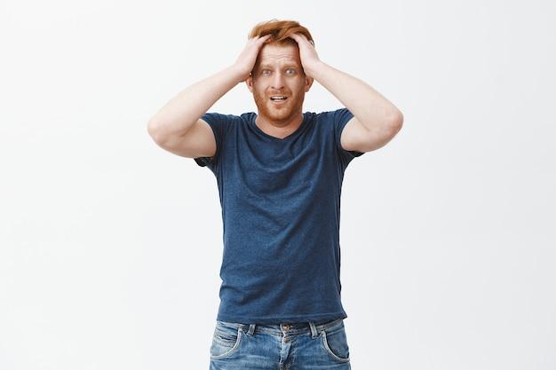 Guy comienza a entrar en pánico. hombre de jengibre atractivo nervioso y ansioso con barba, tocando el cabello, mirando sorprendido y preocupado