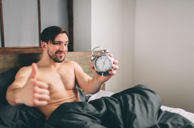 Guy se está despertando. hombre sujetando un reloj despertador barbudo hombre desnudo mostrando los pulgares para arriba en la cama