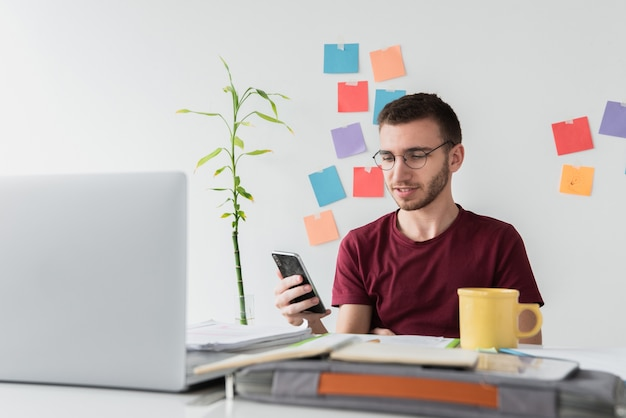 Guy en un escritorio de oficina mirando su teléfono