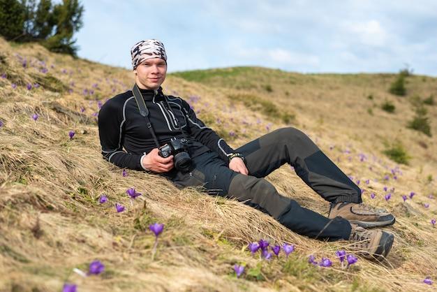 Guy fotógrafo en un traje turístico se encuentra en un claro y fotografía flores de azafrán