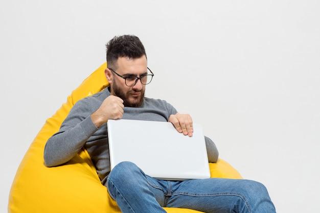 Guy frustra mientras está sentado en la silla del puf amarillo