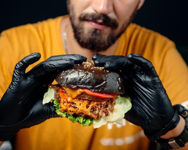Guy en guantes negros tiene una jugosa hamburguesa con queso en pan integral