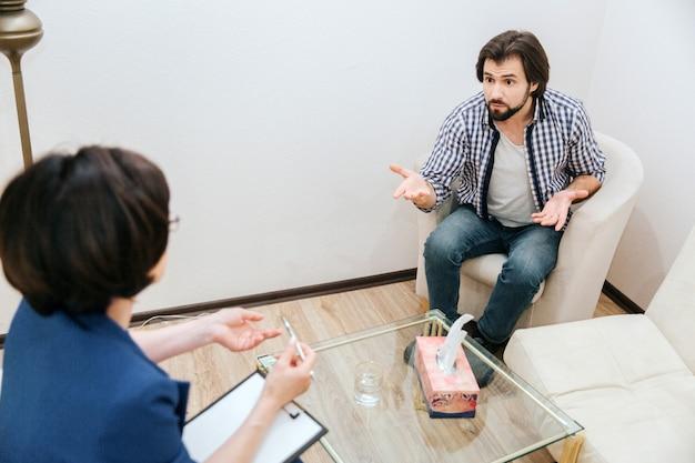 Guy está hablando con el doctor. el es muy emocional. también el hombre está saludando con la mano. el quiere probar algo. el terapeuta lo escucha con mucha atención.