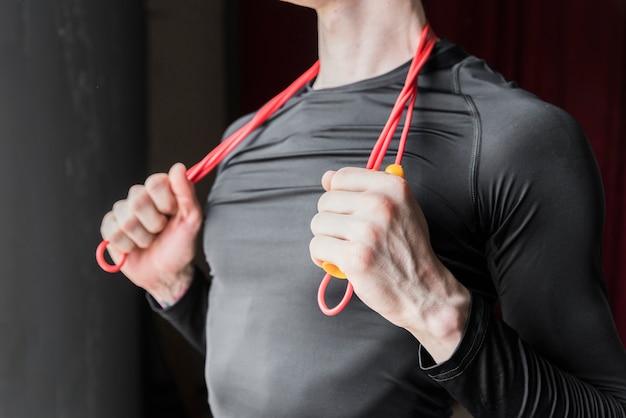 Guy holding saltar la cuerda colocada en el cuello