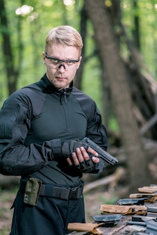 Guy in the woods prueba sus armas para disparar deportes