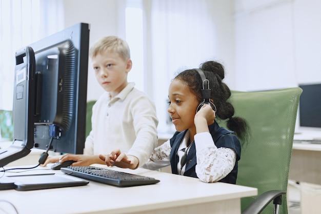 Guy y la niña están sentados a la mesa. niña africana en la clase de informática. niños jugando juegos de computadora.