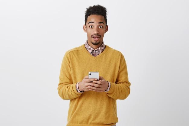Guy recibió un mensaje increíble. guapo americano sorprendido con corte de pelo rizado con smartphone