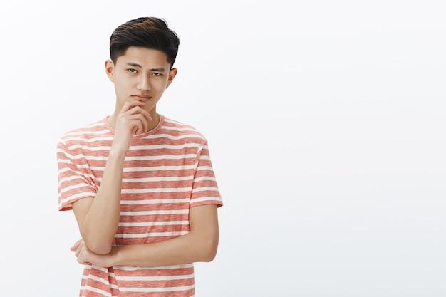 Guy sabe lo que necesitamos. retrato de inteligente y creativo, guapo, joven y determinado estudiante asiático en camiseta a rayas sonriendo satisfecho de sí mismo de pie en actitud pensativa con la mano en la barbilla
