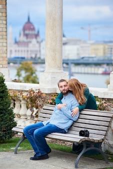 Guy está sentado en el banco, la niña está parada detrás y se inclinó para besarlo con la escena de la arquitectura europea.
