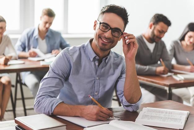 Guy sonriendo mientras toma notas