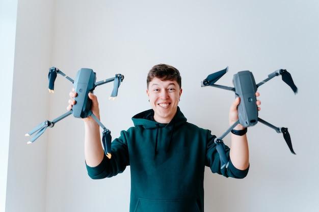 Guy sostiene dos quadrocopters contra una pared.