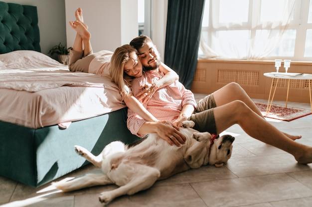 Guy y su novia descansan en el dormitorio. feliz pareja mirando amorosamente a su mascota que quiere jugar.