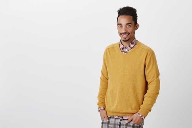 Guy sueña con convertirse en un médico famoso. amistoso estudiante afroamericano ordinario de buen aspecto en jersey amarillo tomados de la mano en los bolsillos y sonriendo cortésmente, esperando el correo en la oficina de correos