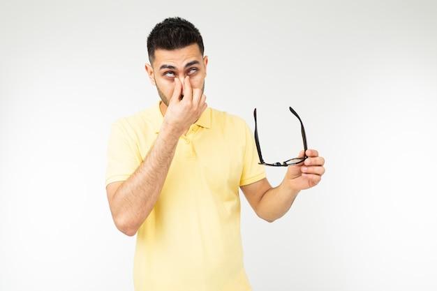 Guy tiene los ojos secos quitándose gafas sobre un fondo blanco.