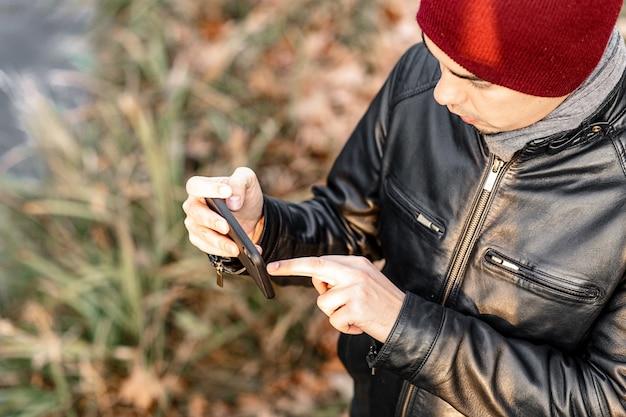 Guy tiene un teléfono en la mano y toma una foto