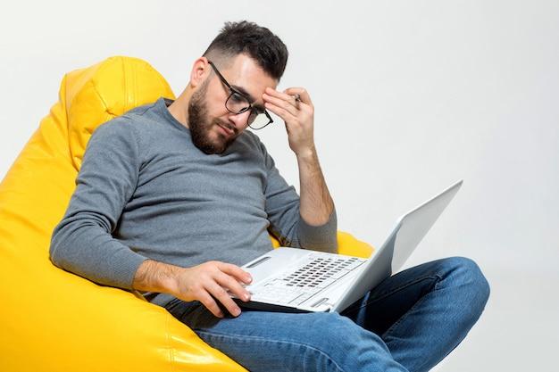 Guy trabaja con la computadora portátil mientras está sentado en una silla amarilla del puf