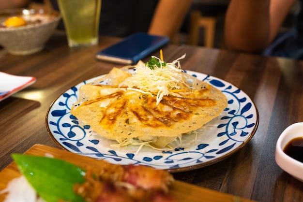 Gyoza o jiaozi frito en la placa en la tabla de madera en restaurante japonés.