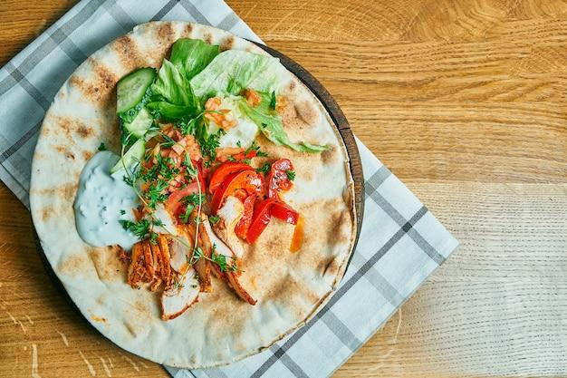 Gyros griegos con yogurt, pollo, pepino y tomates en una mesa de madera. comida de la calle