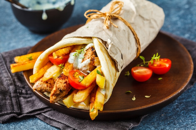 Gyros souvlaki envuelve en pan de pita con pollo, papas y salsa tzatziki.