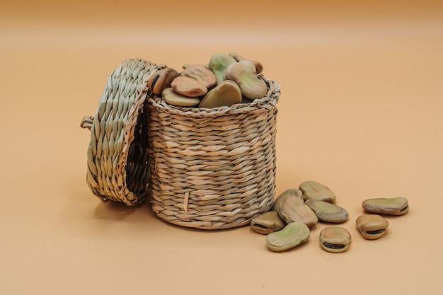 Habas secas orgánicas saludables en una cesta de paja