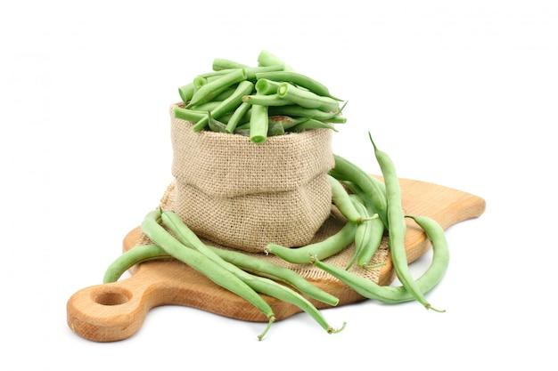 Habas verdes frescas en una tabla de cortar.