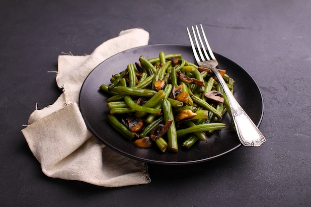 Habas verdes fritas con champiñones en estilo oriental en una placa negra sobre un fondo negro