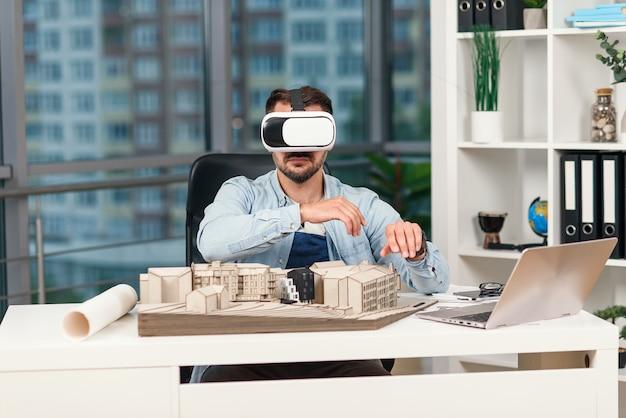 Hábil arquitecto masculino revisando proyecto arquitectónico con gafas vr en la oficina moderna.