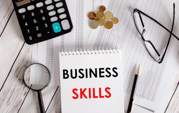 Habilidades empresariales escritas en un bloc de notas blanco cerca de una calculadora, dinero en efectivo, gafas, una lupa y un bolígrafo. concepto de negocio