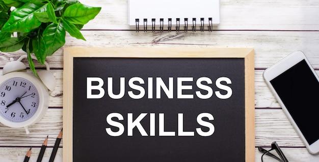 Habilidades empresariales escritas en una superficie negra cerca de lápices, un teléfono inteligente, un bloc de notas blanco y una planta verde en una maceta