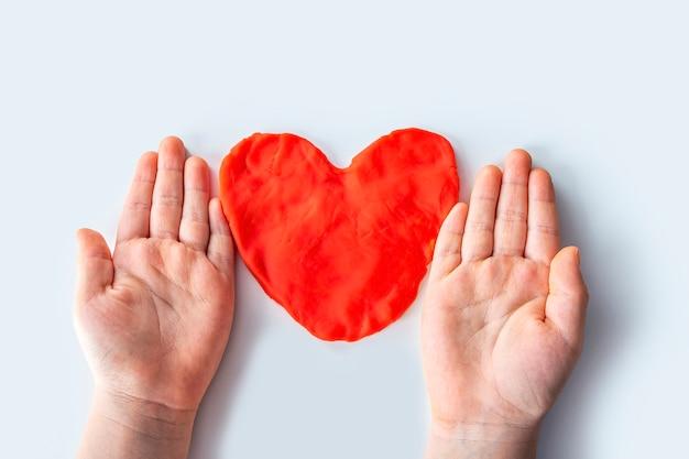 Las habilidades motoras finas. creatividad de los niños. modelado de plastilina para el desarrollo infantil en casa. manos del niño creando corazón de masa roja para modelar. día de san valentín.