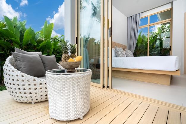 Habitación con balcón y jardín verde.