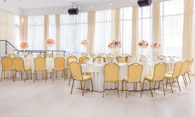 Habitación bellamente decorada con mesas cubiertas con flores en el restaurante.