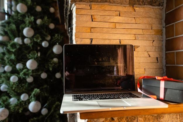 Habitación decorada para año nuevo sin gente portátil con pequeñas cajas de regalo de cerca en una antigua casa de madera