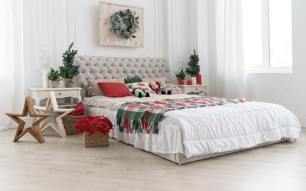 Habitación decorada para vacaciones de navidad con árboles y flores en sala blanca