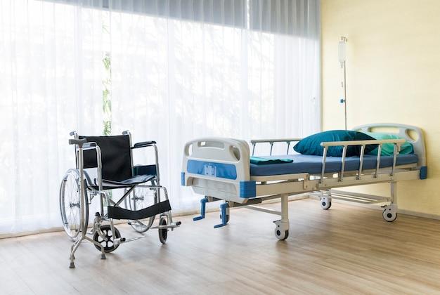 Habitación de hospital con cama vacía, equipo de infusión, líquido intravenoso y sillas de ruedas.
