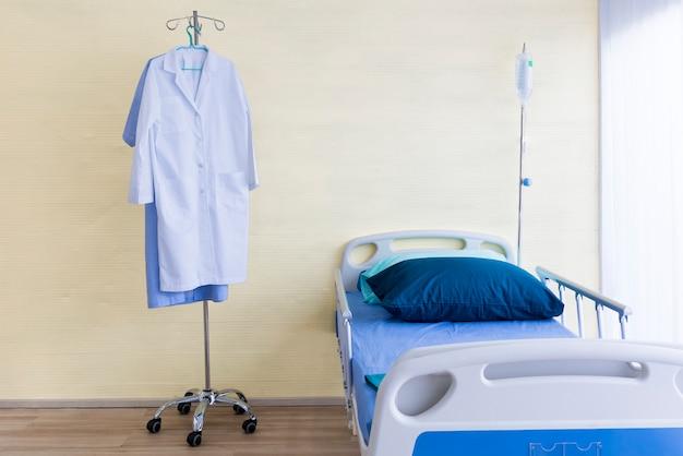 Habitación de hospital con cama vacía, equipo de infusión, líquido intravenoso y suite médica.