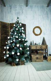 Habitación interior decorada de navidad y año nuevo con regalos y árbol de año nuevo.