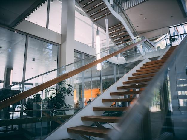 Habitación moderna con escalera de madera durante el día.