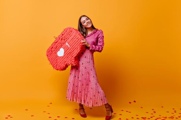 En la habitación con pared de cartón naranja hay una elegante mujer de cabello castaño con falda larga, sosteniendo un gran cartel de instagram. foto tomada en colores naranja y rosa.