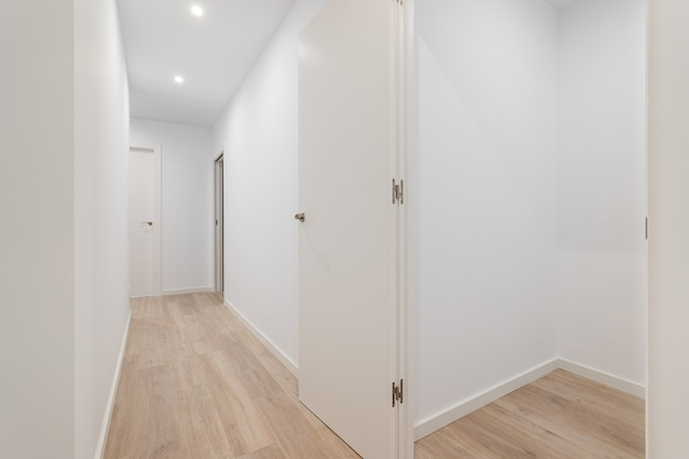 Habitación pequeña vacía con paredes blancas y pasillo que conduce al apartamento de otras habitaciones después de la renovación