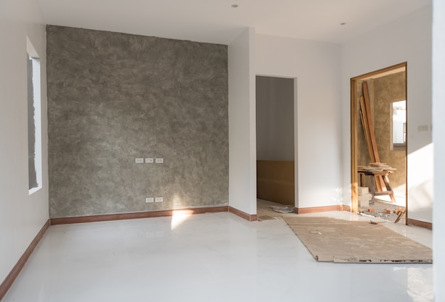 Habitación renovada con piso y pared de cemento tipo loft.