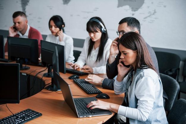 Habitación ruidosa. jóvenes que trabajan en el centro de llamadas. se acercan nuevas ofertas